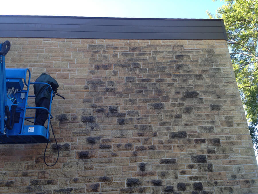 Pressure washing block wall.